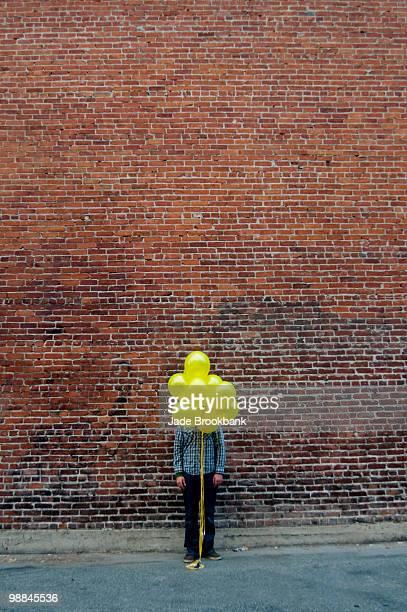 Man standing behind yellow balloons