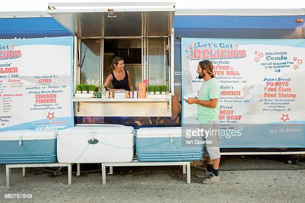 Man standing beside fast food trailer speaking to woman inside trailer