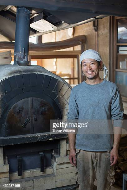 A man standing beside his stone oven