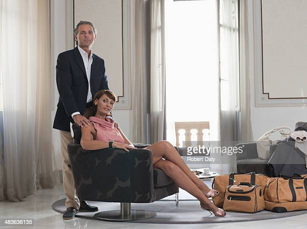 Man standing beside of woman sitting on chair
