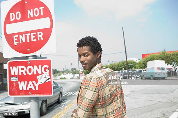 man standing beside street signs - wrong way stock pictures, royalty-free photos & images