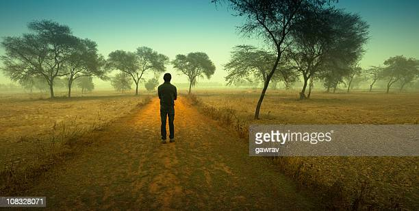 man standing between a country road - between stock pictures, royalty-free photos & images