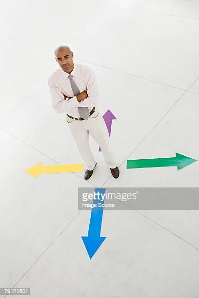 Man standing between arrows