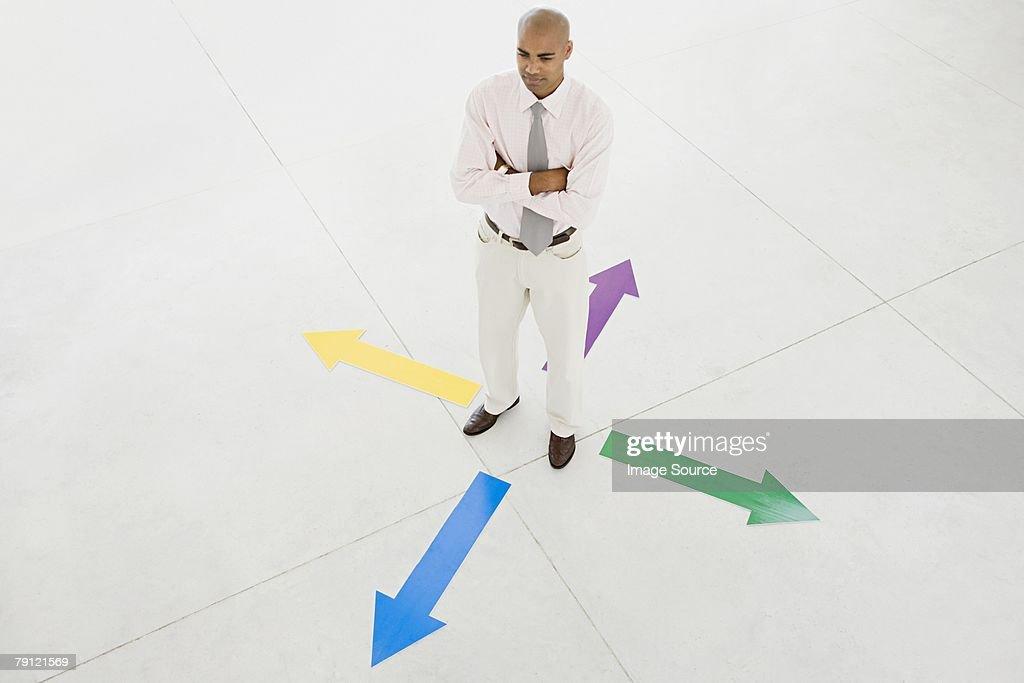 Man standing between arrows : Stock Photo