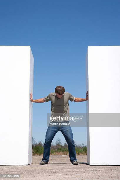 man standing between two walls outdoors pushing - pushing stock pictures, royalty-free photos & images