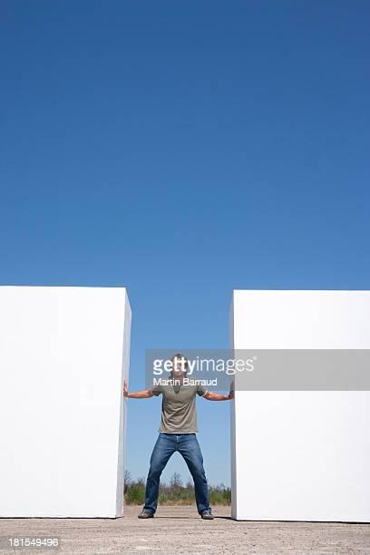 homem em pé entre duas paredes ao ar livre, levando - empurrando - fotografias e filmes do acervo