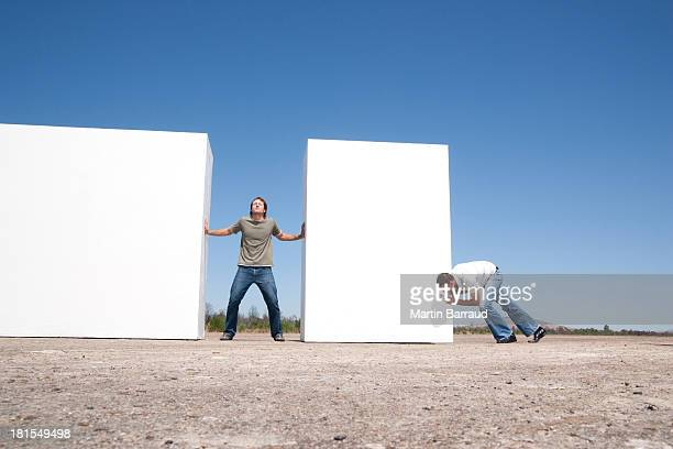 Man standing between two walls pushing outdoors with adversary
