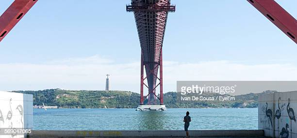 Man Standing By 25 De Abril Bridge Against Sky