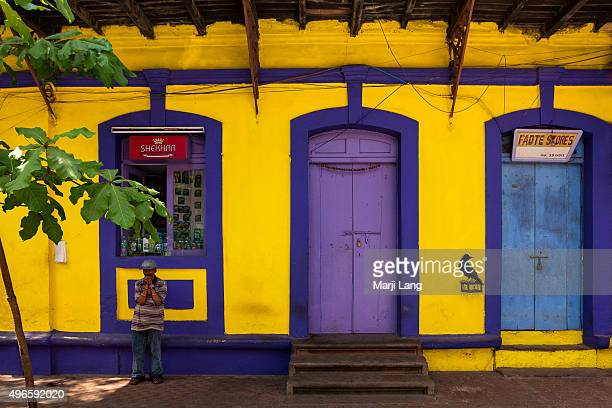 Man standing by a colorful old colonial building of Panjim in Goa a former Portuguese enclave in India