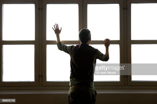 man standing by a window sweden. - claustrophobia stock photos and pictures
