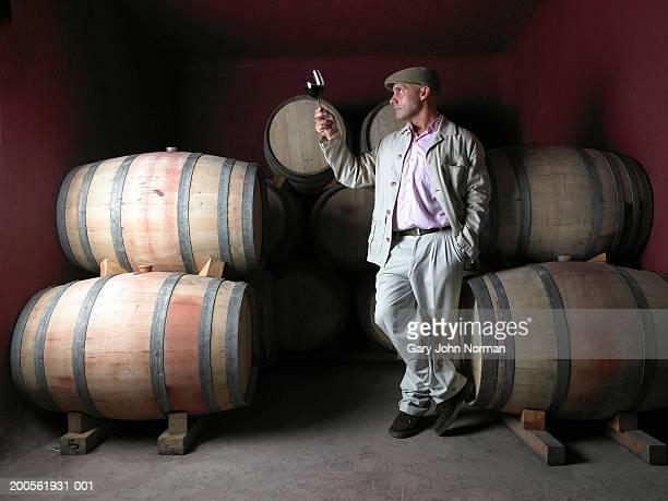 Man standing by barrels in wine cellar