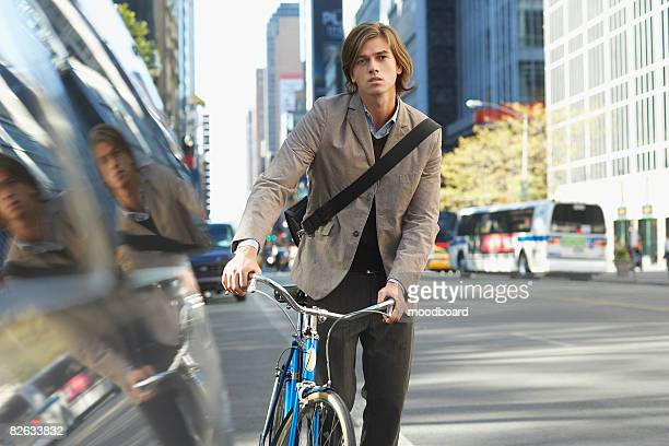 Man standing by bicycle on busy street, portrait