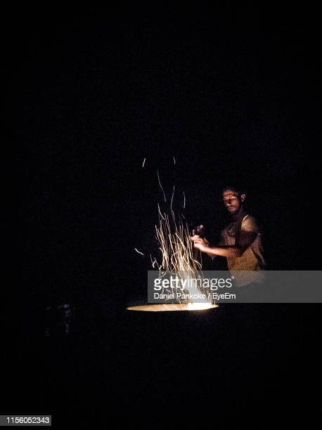 man standing by bonfire at night - daniel funke stock-fotos und bilder