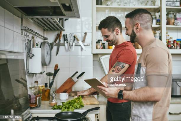 man standing by boyfriend preparing food at home - gay couple stock pictures, royalty-free photos & images