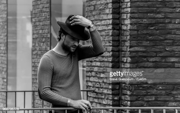 Man Standing By Brick Wall