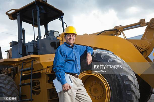 Man standing by bulldozer with tablet, portrait