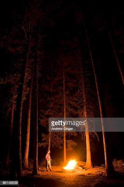 Man standing by campfire in trees at night