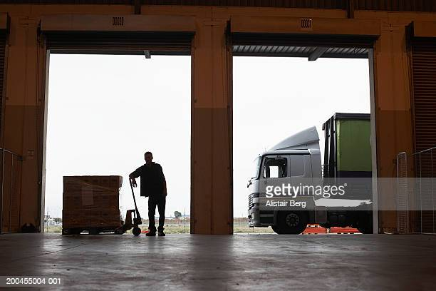 Man standing by delivery on pallet at entrance to warehouse