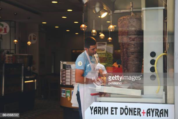 man standing by doner kebab at market - doner kebab stock photos and pictures