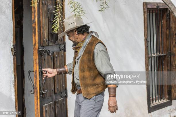 man standing by door of building dressed as cowboy - steven cottingham stock-fotos und bilder