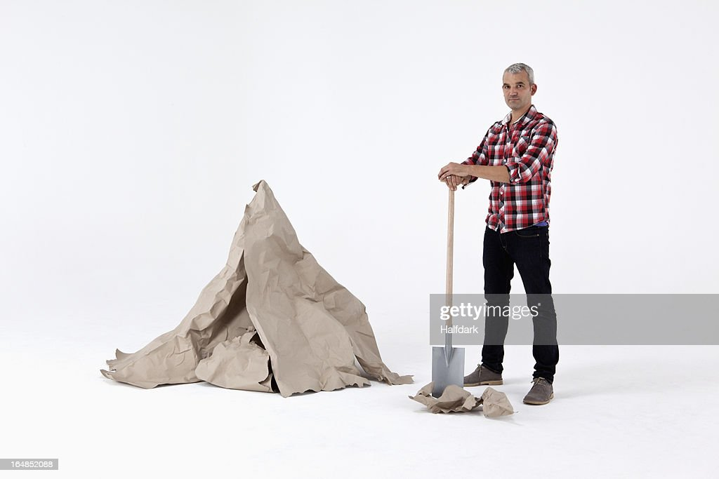 A man standing by dug up construction paper rock, next to an artificial paper boulder : Stock Photo