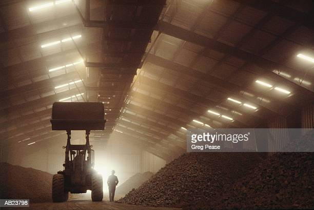 Man standing by earth mover in iron ore storage facility, silhouette