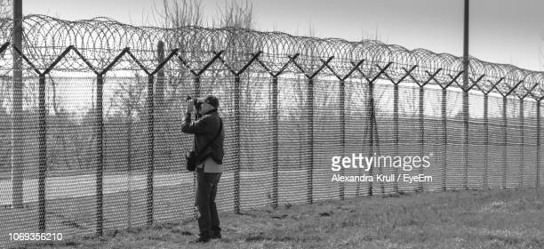 Man Standing By Fence Against Sky