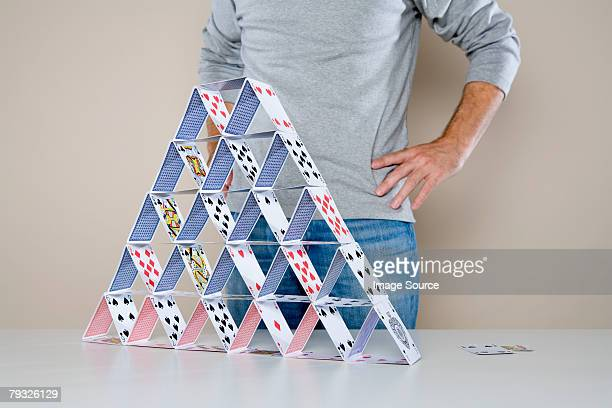 Man standing by house of cards