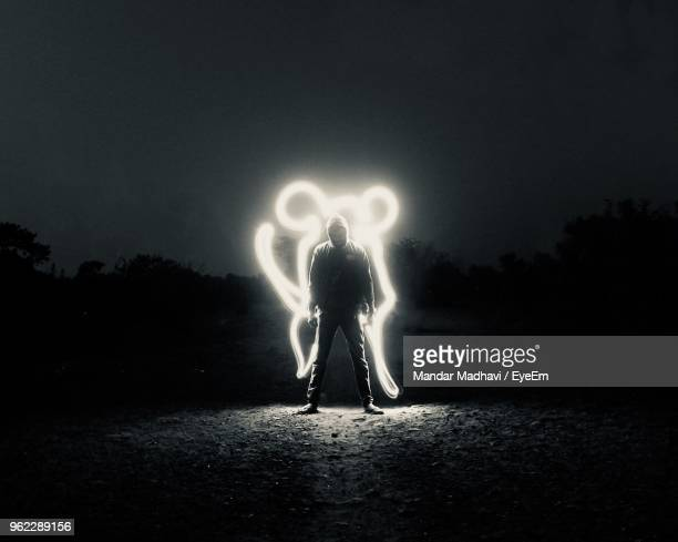 man standing by light painting on field at night - lichtmalerei stock-fotos und bilder