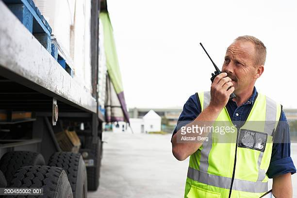 man standing by lorry using walkie-talkie - watchmen stock pictures, royalty-free photos & images