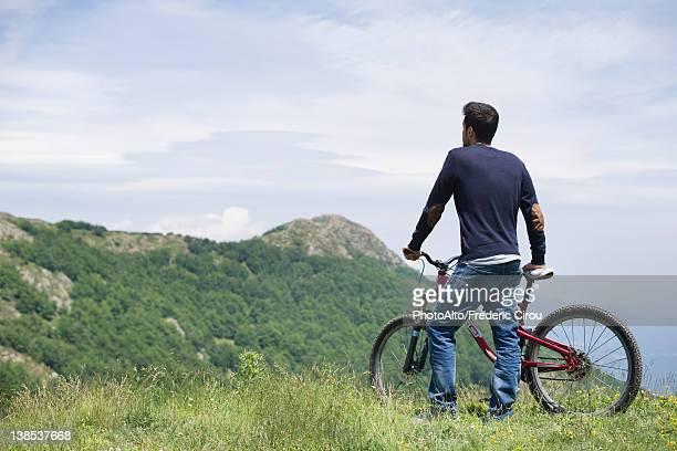 Man standing by mountain bike, enjoying scenic mountain view, rear view