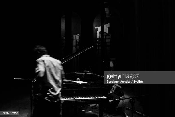 Man Standing By Piano In Darkroom