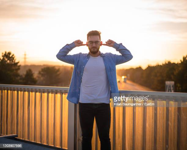 man standing by railing with fingers in ears against sky during sunset - fingers in ears stock pictures, royalty-free photos & images
