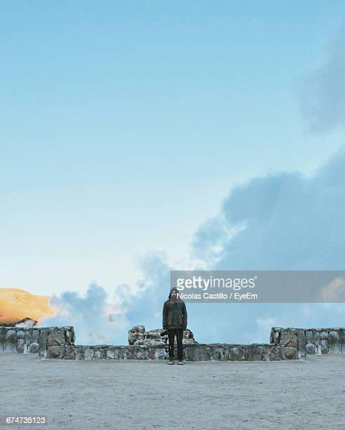 Man Standing By Retaining Wall Against Sky