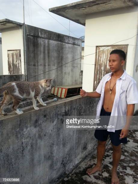 Man Standing By Retaining Wall With Stray Cat On Building Terrace