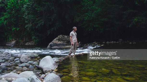 Man Standing By River In Forest