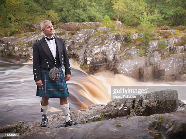 man standing by river in prince charlie outfit with douglas modern tartan - tartan stock pictures, royalty-free photos & images