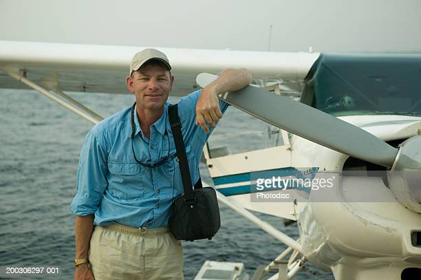 Man standing by seaplane with arm on propeller