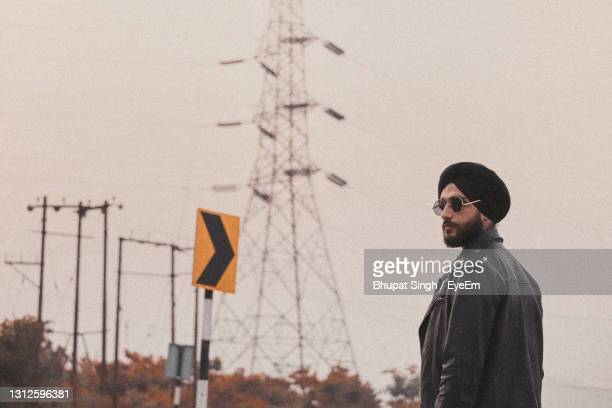man standing by sunglasses against sky - chandigarh stock pictures, royalty-free photos & images