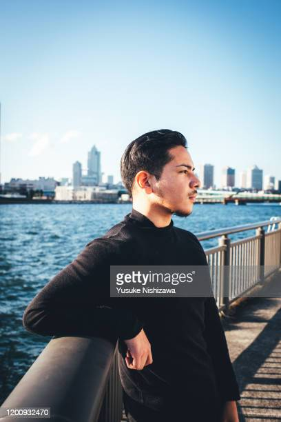 a man standing by the river - yusuke nishizawa stock pictures, royalty-free photos & images