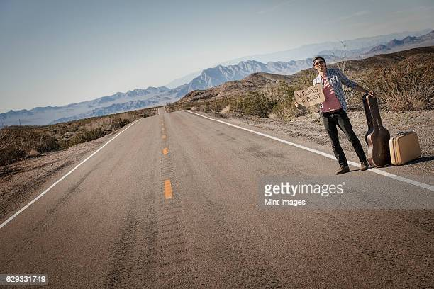 a man standing by the roadside, a hitchhiker with guitar and case, holding a sign saying vegas or bust.  - hitchhiking stock pictures, royalty-free photos & images