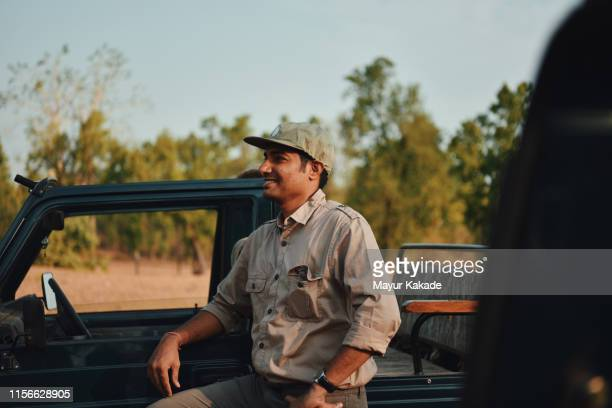 man standing by the safari vehicle - bandhavgarh national park stock pictures, royalty-free photos & images