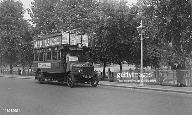 Man standing by Tooting Bec Common as a No49 opened top London 'Tillings Stevens' bus passes on the Tooting Bec Road towards Crystal Palace London...