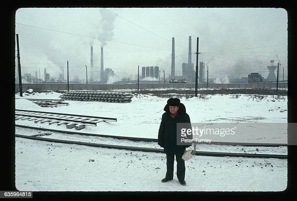 Man Standing by Tracks of Railroad Yard in Chelyabinsk During Winter