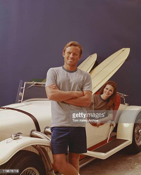 Man standing by vintage mujer en coche, fondo