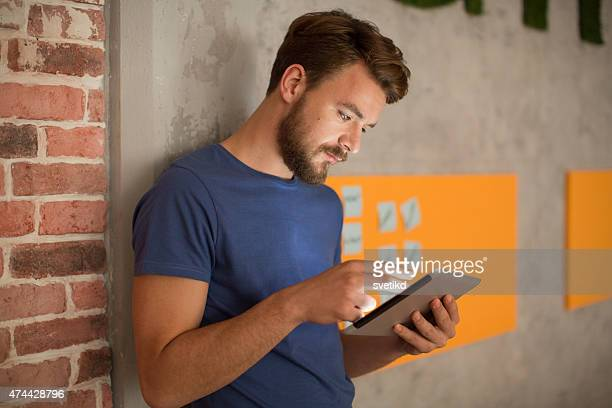 Man standing by wall and using digital tablet.