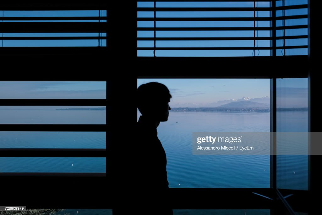Man Standing By Window Against Lake : Stock Photo