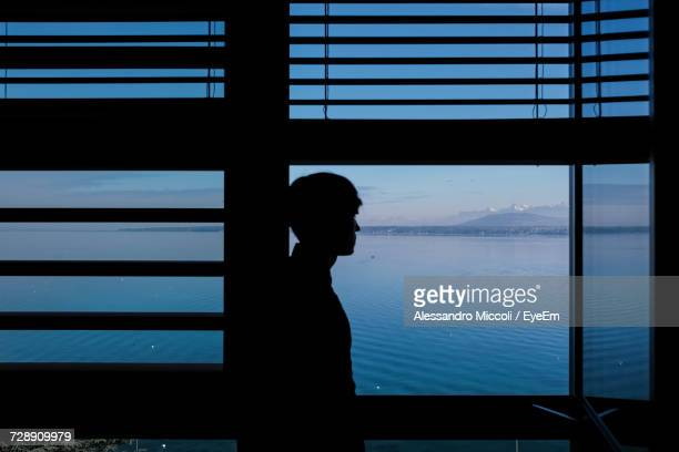 man standing by window against lake - alessandro miccoli fotografías e imágenes de stock