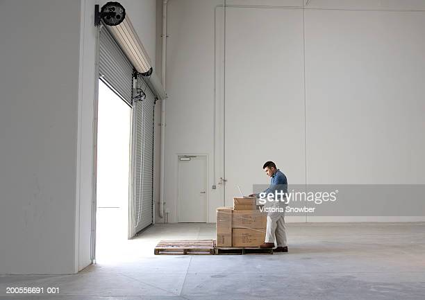 Man standing, examining pallet of cartons, in empty warehouse space