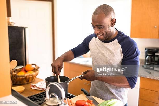 Heureux homme debout dans la cuisine et de préparer la nourriture